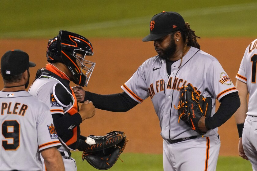 San Francisco Giants starting pitcher Johnny Cueto, right, pats catcher Chadwick Tromp, center, on the chest before being taken out of a baseball game by manager Gabe Kapler during the sixth inning against the Los Angeles Dodgers, Saturday, Aug. 8, 2020, in Los Angeles. (AP Photo/Mark J. Terrill)
