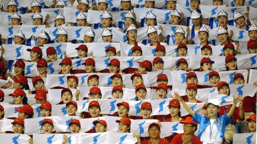 North Korean cheerleaders hold the unified Korea flag during the Summer Universiade 2003 in Daegu, South Korea.