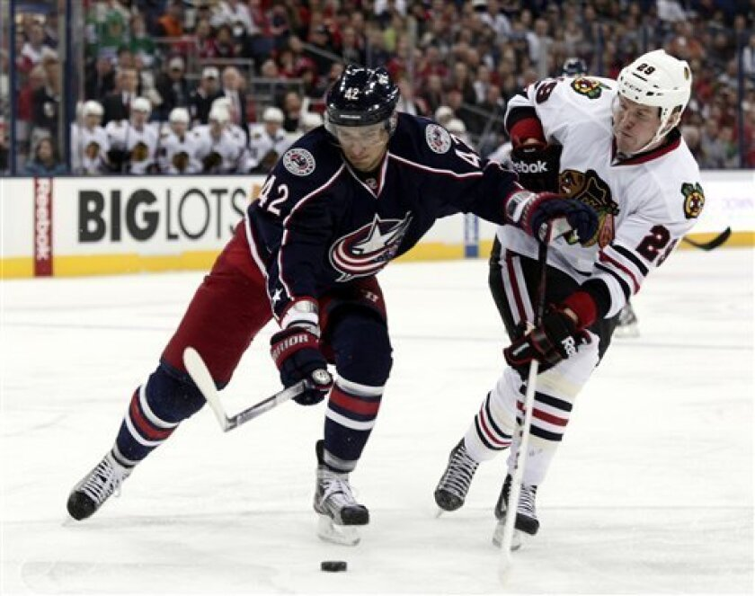 Columbus Blue Jackets' Artem Anisimov, left, of Russia, works for the puck against Chicago Blackhawks' Bryan Bickell during the first period of an NHL hockey game in Columbus, Ohio, Thursday, March 14, 2013. (AP Photo/Paul Vernon)
