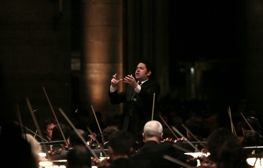 Venezuelan maestro Gustavo Dudamel, shown conducting the Orchestre Philharmonique de Radio France during rehearsals at the Notre-Dame de Paris cathedral late last month, issued a statement Thursday defending his appearance in Maracay, Venezuela, at a performance attended by Venezuelan President Nicolas Maduro. Three protesters were slain in clashes between pro- and anti-government groups on Wednesday.