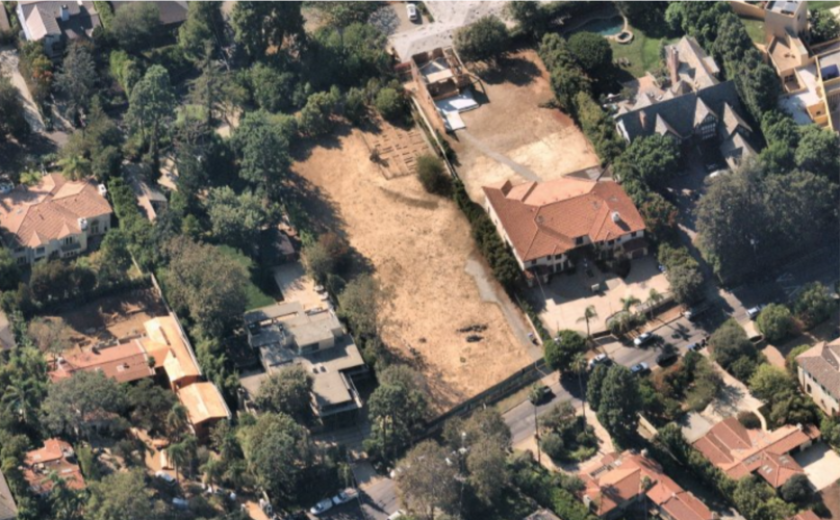 An aerial view of a dirt plot in the middle of landscaped plots with large houses and trees.