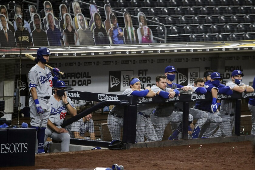 The Dodgers watch from the dugout Monday while playing the Padres at Petco Park, the future site of MLB playoff games.