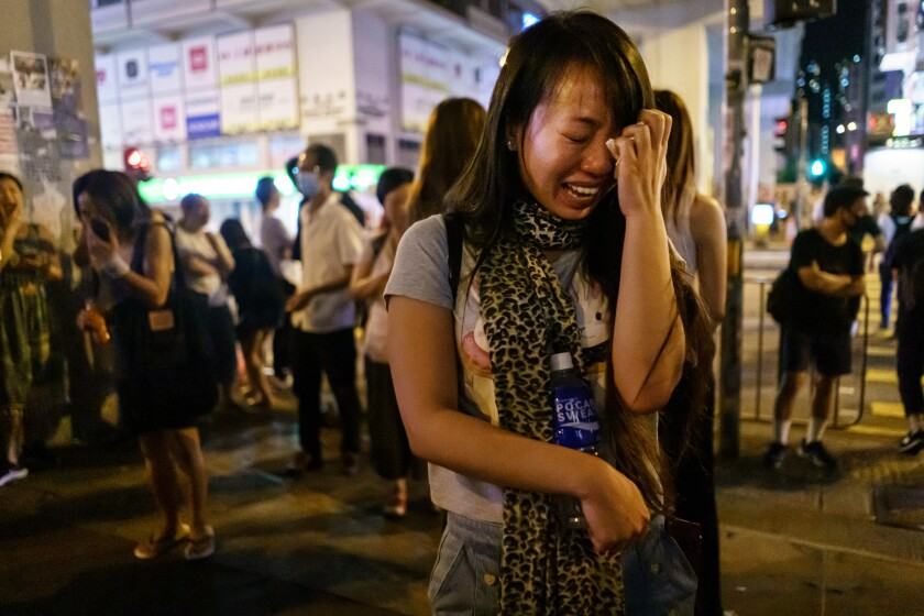Pino Tong cries Sept. 11 as she and others pay respects to those injured in a clash with police in Hong Kong.