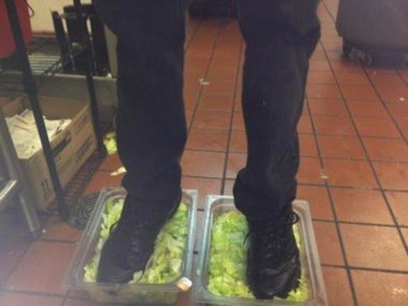 A photo posted on 4Chan showing a Burger King employee stepping in two tubs of lettuce
