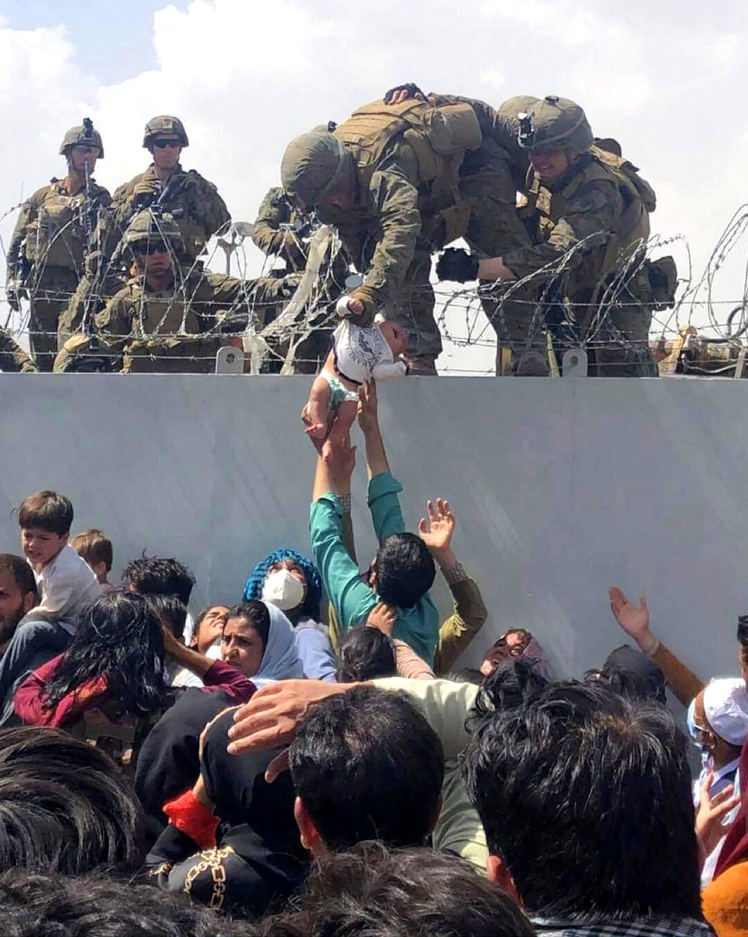 A U.S. Marine grabs an infant over a fence of barbed wire during an evacuation at Hamid Karzai International Airport