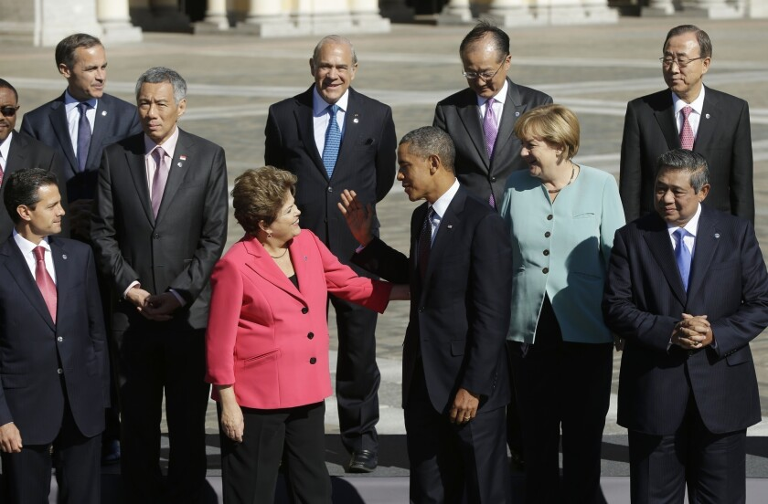 Brazilian President Dilma Rousseff and President Barack Obama greet each other as they join other world leaders for the group photo at the G-20 summit at Konstantin Palace in St. Petersburg, Russia.