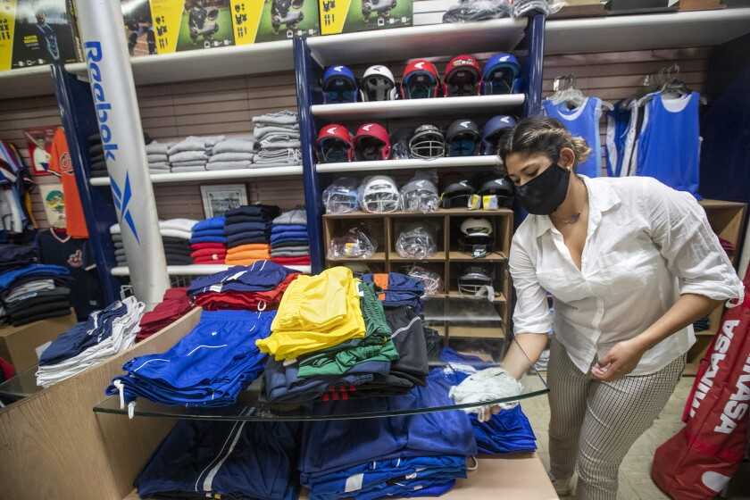 Daniela Prieto, an employee at Deportes Prieto in Boyle Heights, disinfects inside the store.