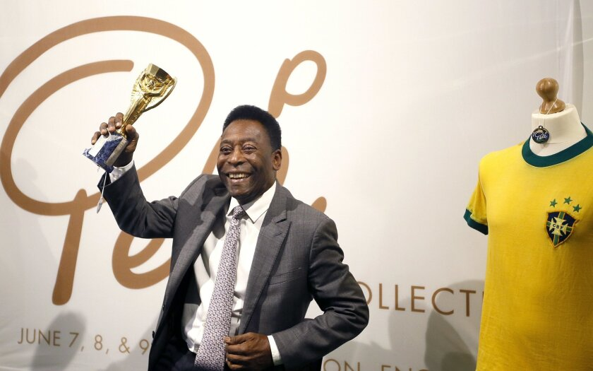 Pele,  former Brazilian soccer star holds up his copy of the Jules Rimet Trophy, during a media opportunity in London, Wednesday, June 1, 2016. The three-time World Cup Champion, FIFA Player of the Century and Brazilian Football icon, will offer his vast collection of memorabilia, awards, personal