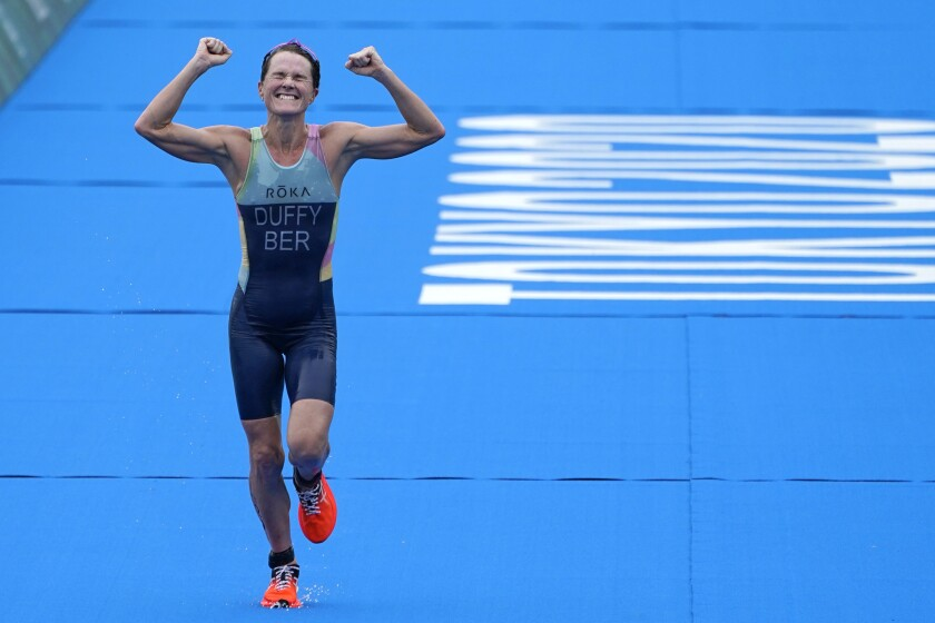 Flora Duffy of Team Bermuda celebrates as she approaches the finish line to win the gold medal during the women's individual triathlon competition at the 2020 Summer Olympics, Tuesday, July 27, 2021, in Tokyo, Japan. (AP Photo/David Goldman)