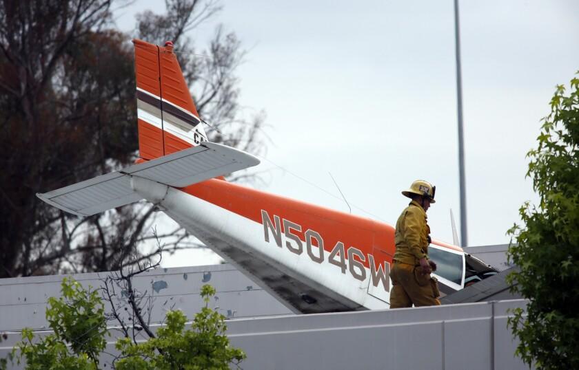 On Sunday, a firefighter surveys the scene where a single-engine plane crash-landed on a building in Pomona.