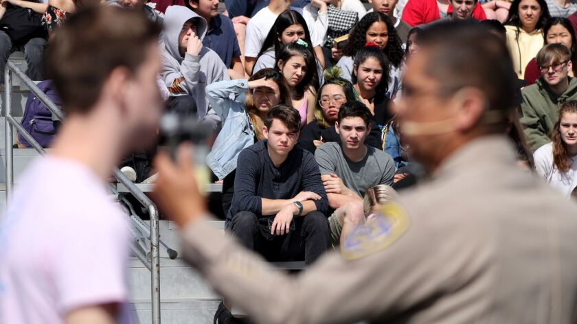 Students watch as a California Highway Patrol officer gives a mock alcohol breath test to a student
