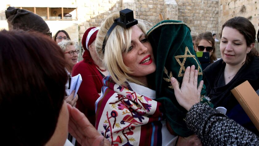 "A member of the liberal Jewish religious group Women of the Wall wears phylacteries and ""Tallit"", a"