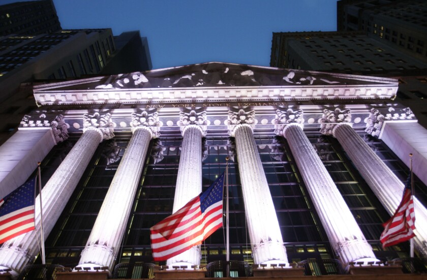 Flags fly in front of the New York Stock Exchange.