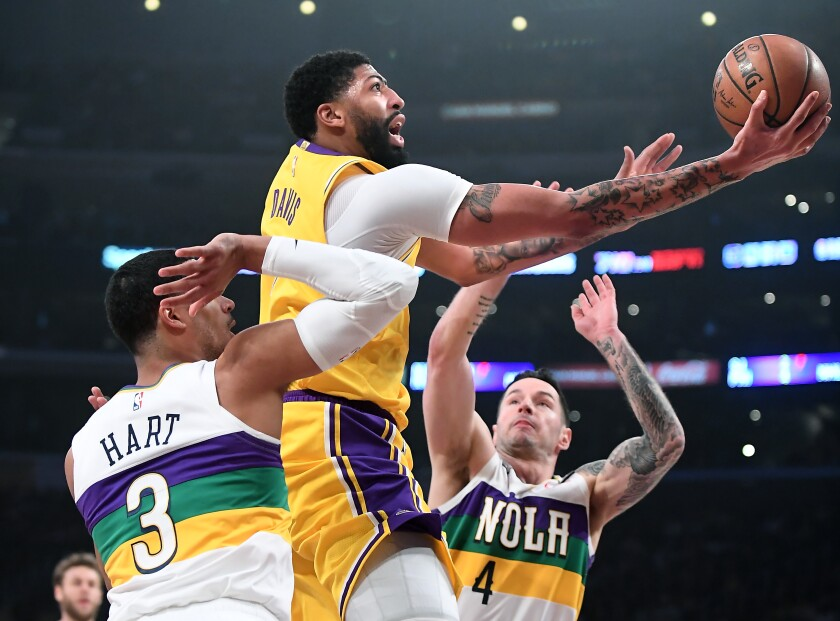 Lakers forward Anthony Davis splits Pelicans defenders Josh Hart and JJ Redick (4) for a layup during a game Feb. 25, 2020, at Staples Center.