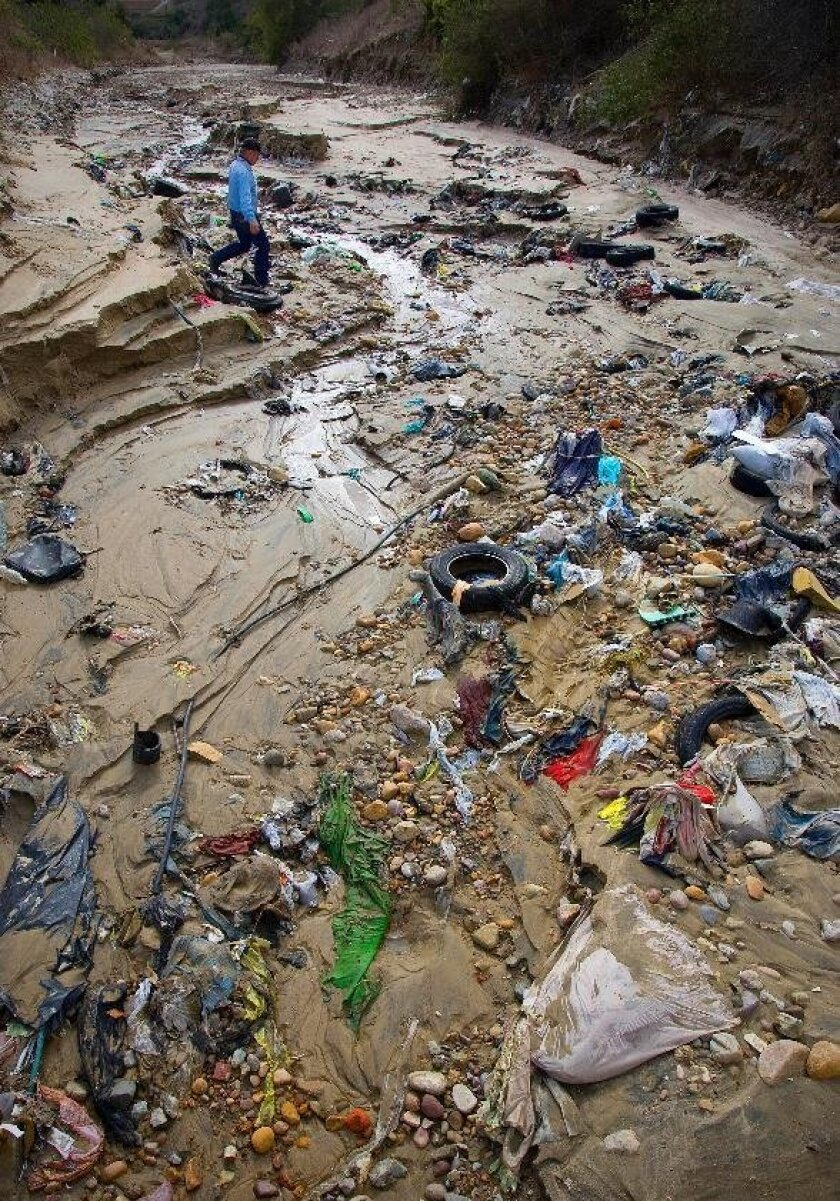 Debris and silt clog culverts under Monument Road in San Diego in this file photo. It's the kind of problem that can lead to increased bacteria in local waterways, something regulators are trying to control.