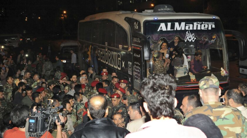 In this photo released by the Syrian official news agency SANA, soldiers and residents gathering nea