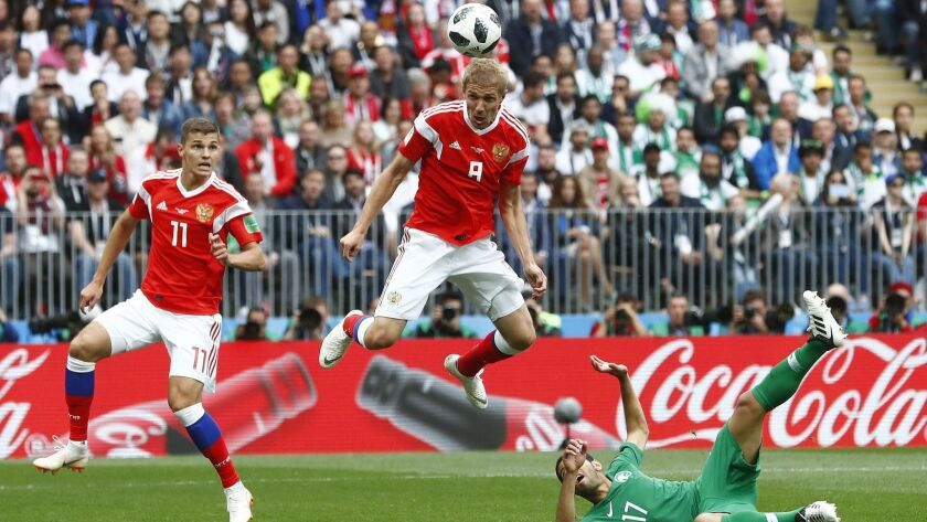 Russia's Yuri Gazinsky heads the ball to score the opening goal during the group A match between Rus