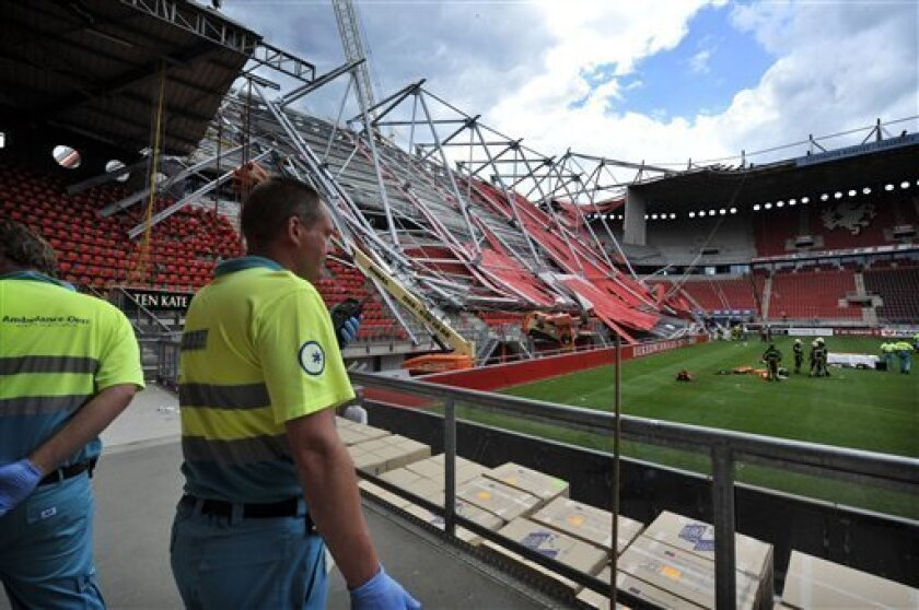 Ambulance workers are seen inside the Grolsch Veste stadium in Enschede, Netherlands, Thursday, July 7, 2011. A section of a Dutch football stadium collapsed during off-season construction work in trapping people underneath, police said. The mayor of Enschede says at a press conference one worker was killed and 10 hospitalized. (AP Photo/Tubantia/Carlo ter Ellen) NETHERLANDS OUT, EDITORIAL USE ONLY, NO SALES, MANDATORY CREDIT
