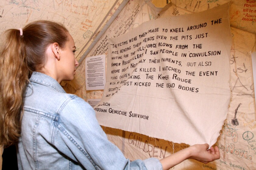 Glendale High School senior Lizzy Kaser reads a quote from a Cambodian genocide survivor, posted in a tent provided to the school by i-Act on Thursday, March 10, 2016. i-Act provided six tents with information about genocides in Armenia, Cambodia, the Holocaust and present-day Darfur.