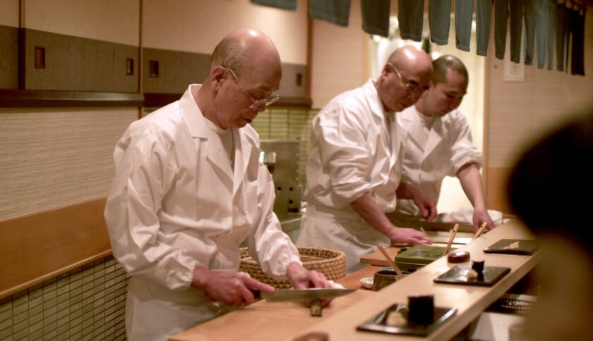 "Jiro at work at the sushi bar with his son Yoshikazu is at his side in ""Jiro Dreams of Sushi."" Photo David Gelb."