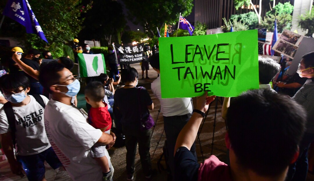"A person holds a placard reading ""Leave Taiwan Be"" as protesters gather at the Chinese Consulate in Los Angeles."