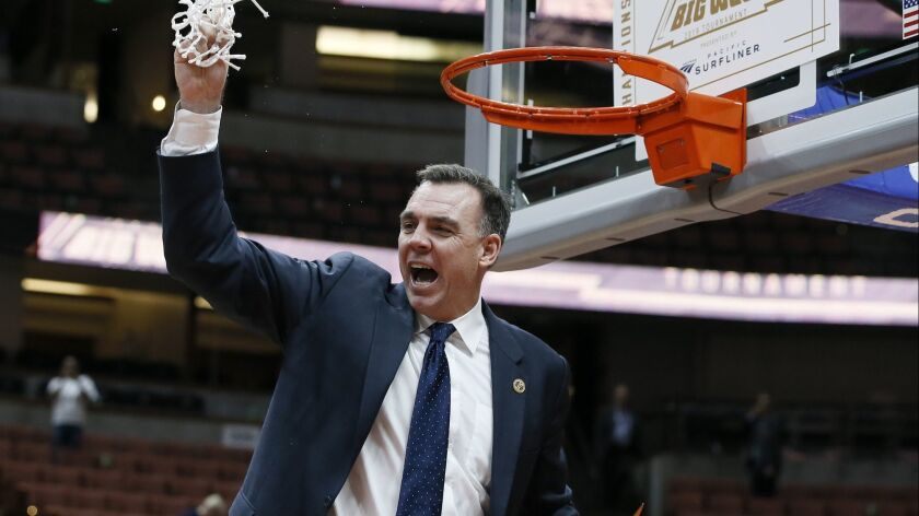 UC Irvine coach Russell Turner celebrates by cutting down the net after his team beat Cal State Fullerton in the Big West tournament title game Saturday.