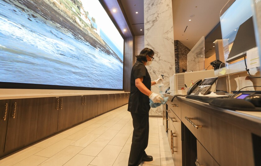 Preparing for reopening, Jane Santo Domingo, an environmental services worker, cleans the front desk area at Sycuan Casino in El Cajon on May 15, 2020.