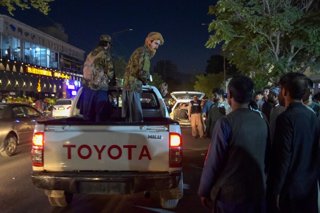 Taliban fighters stand in the bed of a pickup truck outside a hospital as volunteers bring injured people for treatment
