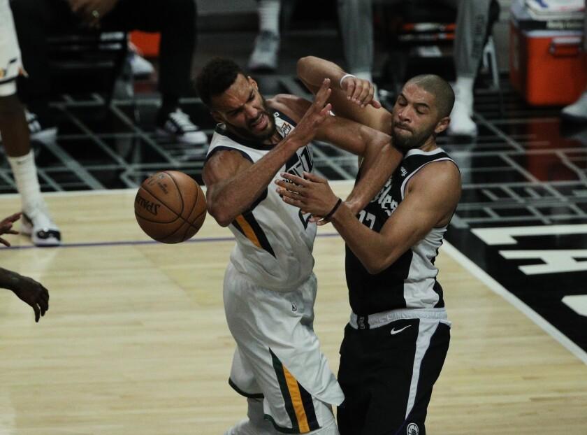 Clippers forward Nicolas Batum, right, battles Jazz center Rudy Gobert for the ball.