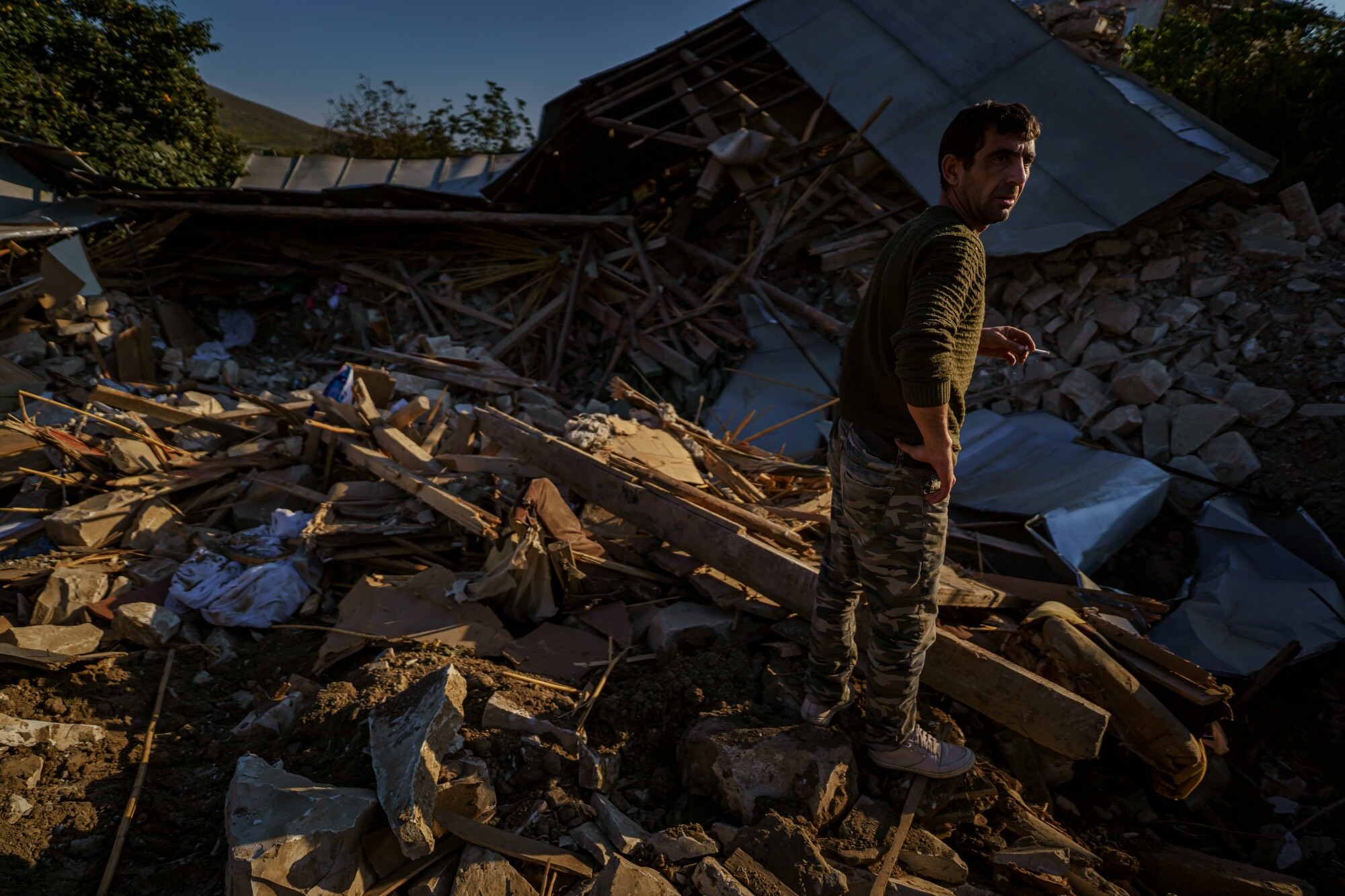 A man stands amid the ruins of a home after a military strike in Nagorno-Karabakh.