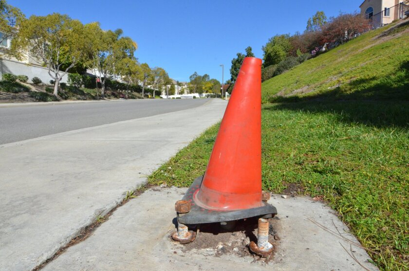 Orange traffic safety cones like this one have temporarily replaced rusting streetlight poles in Oceanside's Rancho Del Oro community. Residents are voting on whether to form an assessment district to pay to permanently replace 669 street lights.