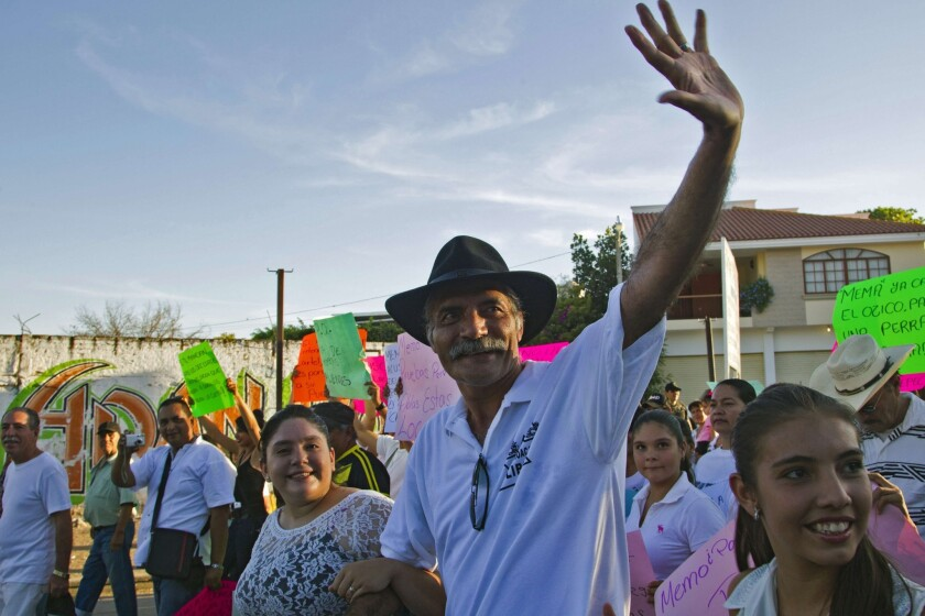 """Jose Manuel Mireles, a leader of a """"self-defense"""" group in Mexico's Michoacan state, waves during a February march to celebrate the anniversary of the groups of civilians who say they took up arms to fight the drug cartels."""