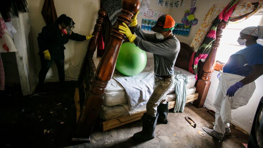 From left, Lupe Bernal, Saul Galvan and Nikki Fields work quickly to dismantle the bedroom furniture