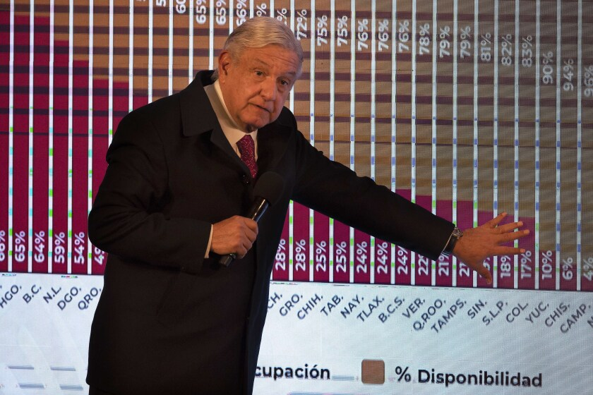 FILE - In this Dec. 18, 2020 file photo, Mexican President Andres Manuel Lopez Obrador points to a graph showing the percentages of hospital beds available, state by state, during his daily news conference at the presidential palace, Palacio Nacional, in Mexico City. López Obrador was working from isolation on Monday, Jan. 25, 2021, a day after announcing that he had tested positive for COVID-19, his interior secretary said. (AP Photo/Marco Ugarte, File)