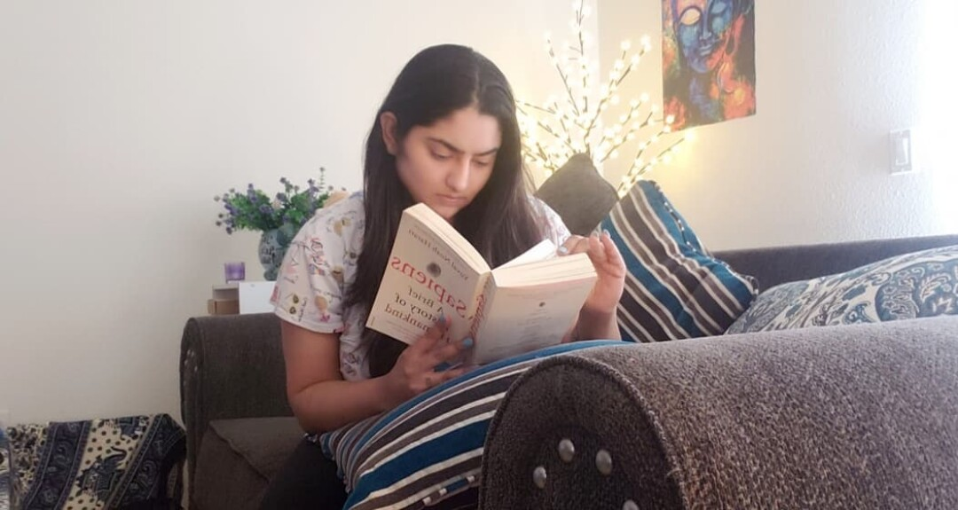 Tanya Sawhney reads at her home Monday night.