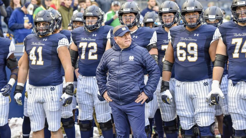 Notre Dame head coach Brian Kelly stands with his team before an NCAA college football game against