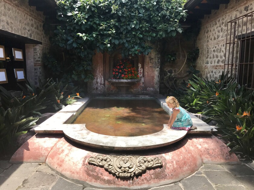 The reporter's daughter, Cora, plays at a fountain in a courtyard at Porta Hotel Antigua, Guatemala