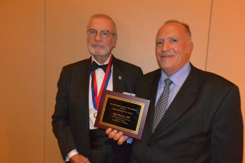 Dr. A. Brent Eastman and Dr. Imad Dandan with his award.