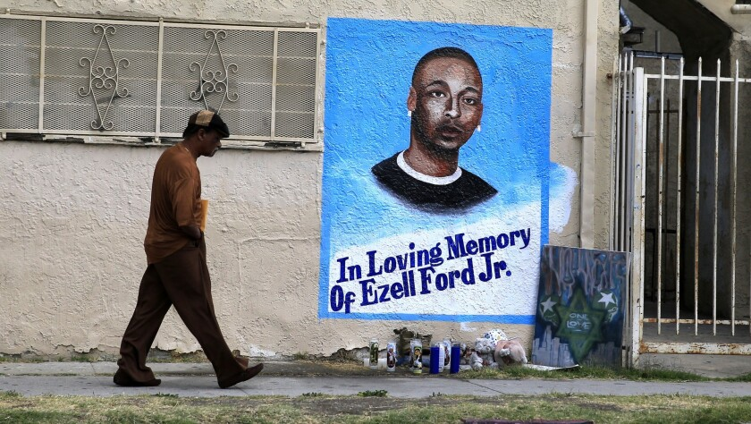 A man walks by a memorial at 65th Street and Broadway in South L.A., where Ezell Ford was killed.