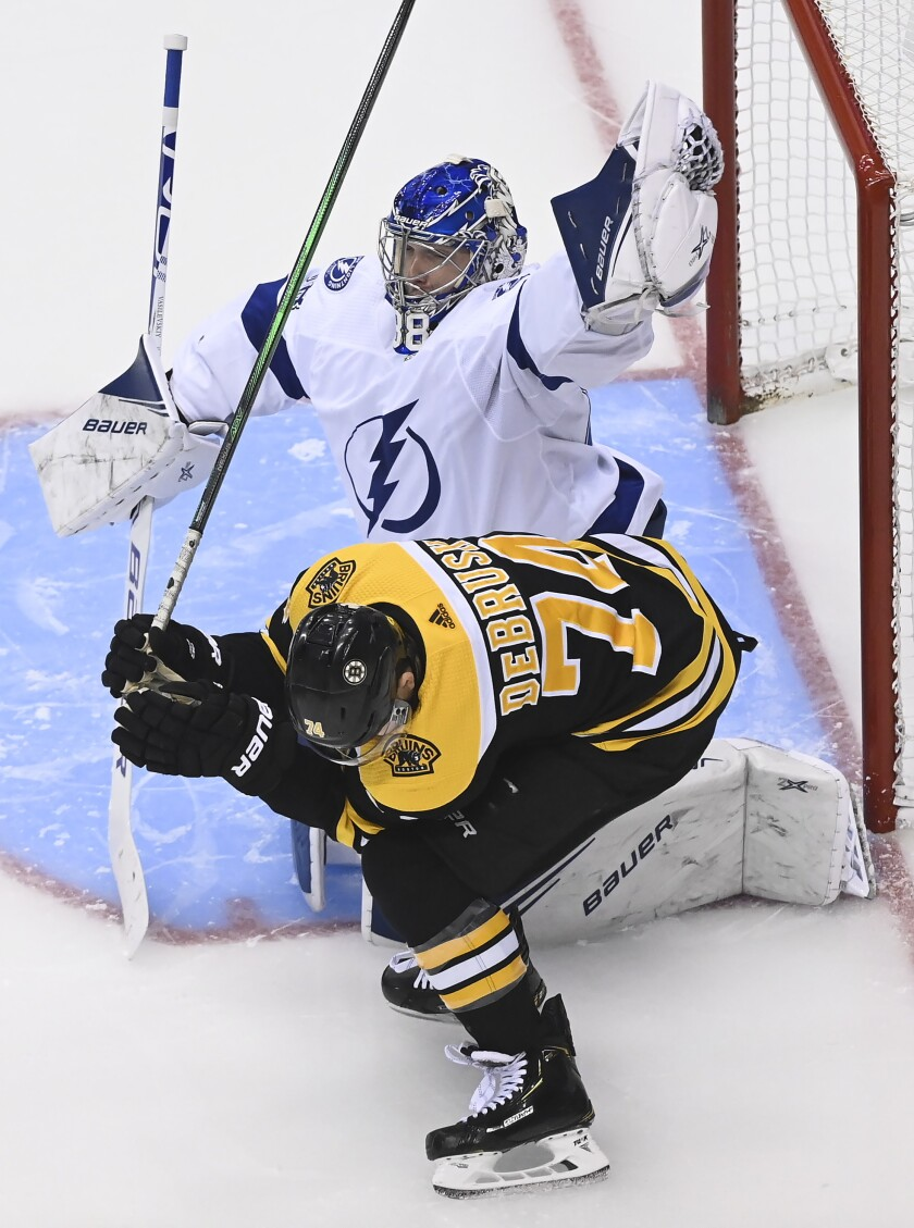Boston Bruins left wing Jake DeBrusk (74) ducks as Tampa Bay Lightning goaltender Andrei Vasilevskiy (88) makes a glove save during the second period of an NHL Stanley Cup playoff hockey game in Toronto, Ontario, Wednesday, Aug. 5, 2020. (Nathan Denette/The Canadian Press via AP)