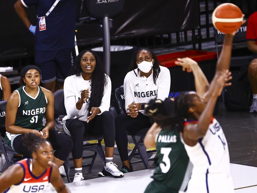 Nigeria guard Erica Erinma Ogwumike watches alongside sisters Chiney Ogwumike and Nneka Ogwumike during a game.
