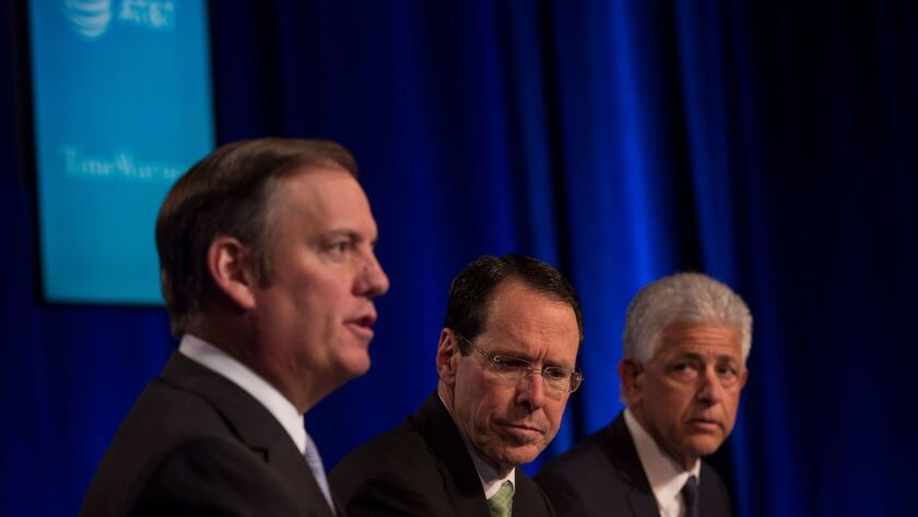 AT&T General Counsel David R. McAtee II, left, AT&T Chief Executive Randall Stephenson and attorney Daniel Petrocelli discuss the Justice Department lawsuit at a news conference this month.