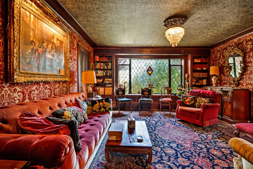 A living room with deep colors, a chandelier, built-in bookcases and Tudor-style diamond-shaped windowpanes.