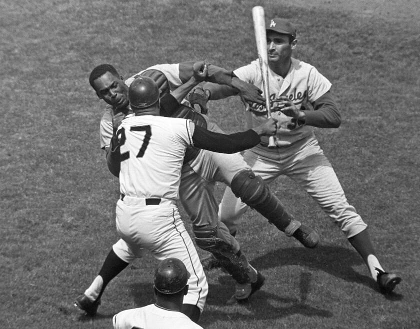 San Francisco pitcher Juan Marichal (27) swings a bat at Dodgers catcher John Roseboro as Dodgers pitcher Sandy Koufax, right, tries to break it up on Aug. 22, 1965.