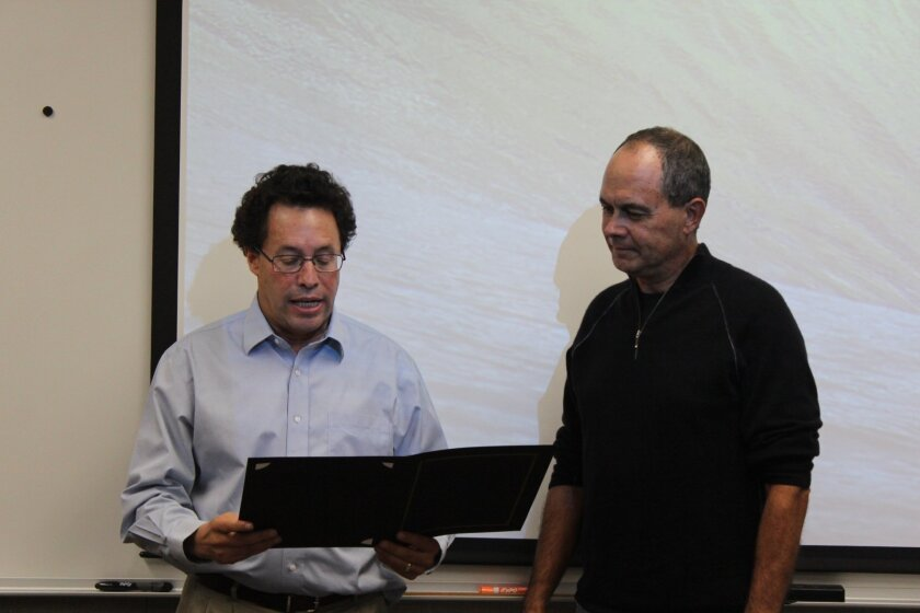 Outgoing board member Jeff Busby, at right, is presented with a certificate of recognition for his work. Courtesy photo