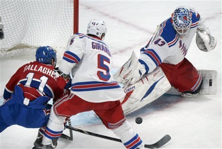 New York Rangers goaltender Martin Biron, right, makes a save against Montreal Canadiens' Brendan Gallagher (11) as Rangers' Dan Girardi defends during first-period NHL hockey game action in Montreal, Saturday, March 30, 2013. (AP Photo/The Canadian Press, Graham Hughes)