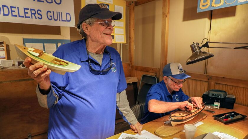 At the San Diego County Fair Woodworking Show James Pitt, left, and Jay MacMaster, right, of the San Diego Ship Modelers Guild, speak to visitors as they work on model ships.