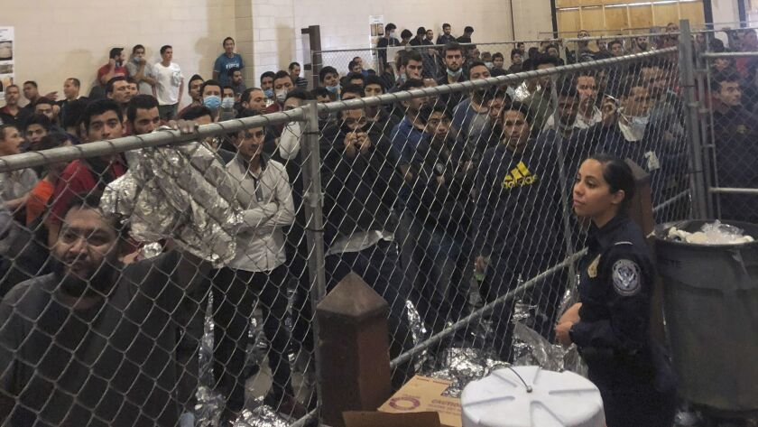 Men stand in a U.S. Immigration and Border Enforcement detention center in McAllen, Texas, Friday, J