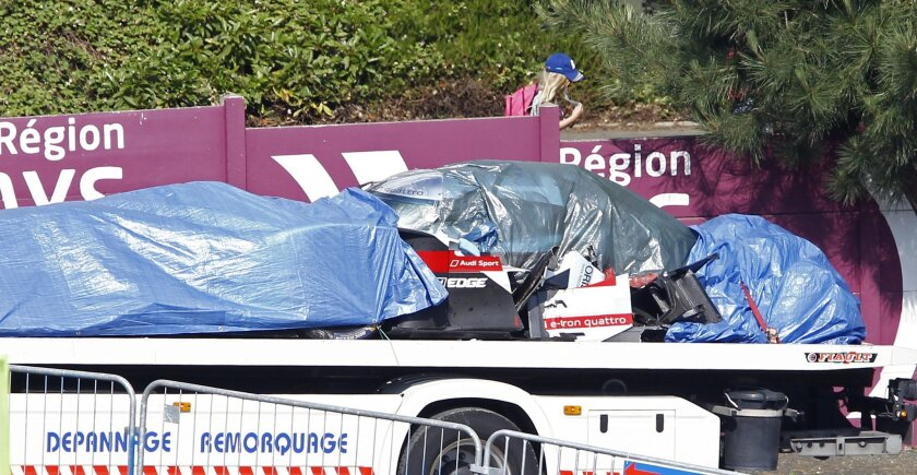 The remains of the Audi R18 E-Tron No1 driven by Loic Duval of France are brought back to the pits after it crashed during a free practice session for the 24-hour Le Mans endurance race, in Le Mans, western France, Wednesday, June 11, 2014. The race will take place here on Saturday June 14 and Sunday June 15.(AP Photo/Remy de la Mauviniere)