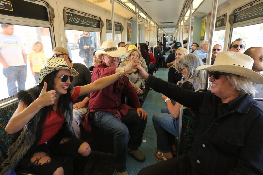 From left; Kat Herrera, Benjamin Hutto, and Brian O' Brien, all friends from Malibu, celebrate as the Expo Line leaves Santa Monica Station. They were heading to Los Angeles to celebrate O' Brien's 65th birthday.